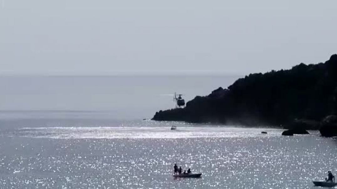 Helikopteri mbush ujë në plazhin e Livadhit për të shuar zjarret rreth Himarës